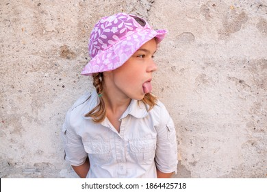 Beautiful teenage girl in a pink hat stands near a stone wall and shows her tongue.
