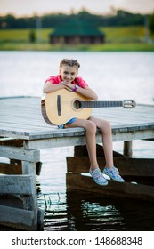 beautiful teenage girl playing a guitar outdoors