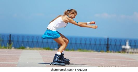 Beautiful teenage girl rollerskating in park