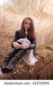 Beautiful teenage girl sitting on a stone wall looking looking straight to camera