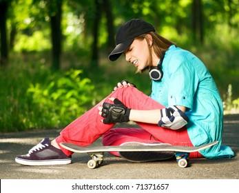 Beautiful teenage girl with skateboard in the green park