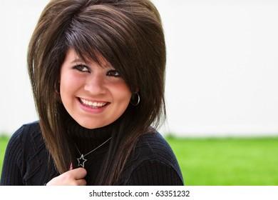 Beautiful teenage girl smiling outside in a black sweater