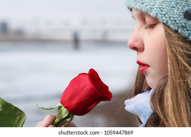 Beautiful teenage girl is sniffing red rose outdoor. Close-up portrait of a girl in profile.
