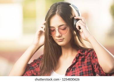 Beautiful teenage girl with sunglasses listening to music
