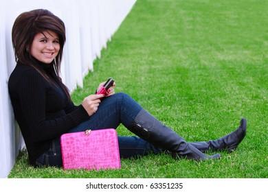 Beautiful teenage girl talking on the phone outside