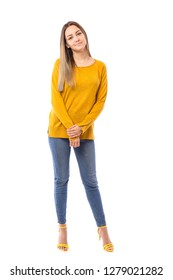 Beautiful teenage girl wearing jeans and yellow sweater posing over white background