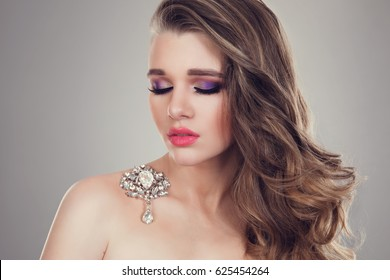 Beautiful teenage girl woman eyes closed with full make up curly hair, curls jewel broach on her shoulder. Evening makeup pink full lips purple yellow sparkly eye shadow big natural brows looking down