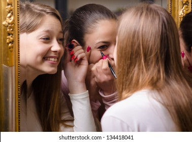 Beautiful teenage girlfriends having fun while putting make up in front of the old mirror.