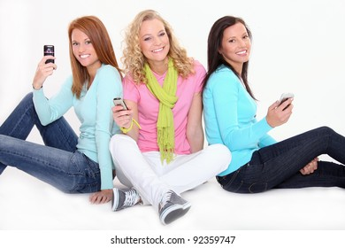Beautiful teenage girls are holding cell phones