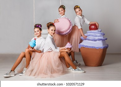 Beautiful teenage model girls in pink tutu or tulle skirts with macaroons, fancy cakes and sweets in studio on white background