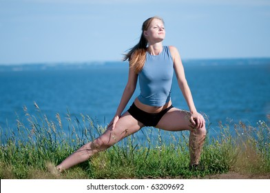 Beautiful teenage sport woman   doing stretching exercise over blue sea landscape. Yoga