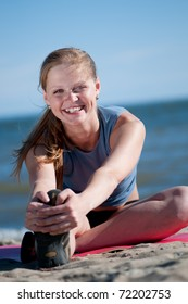 Beautiful teenage sport woman   doing stretching exercise on sand beach. Yoga