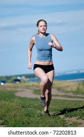 Beautiful teenage sport woman running in sea coast on sunny summer day