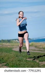 Beautiful teenage sport woman running in sea coast on sunny summer day