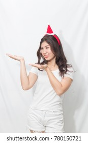 Beautiful teenage young asian woman in white shirt and pants.Her head weared a santa claus hat with hand holding.Smile and cute in Happy vacation new year. Merry christmas.
