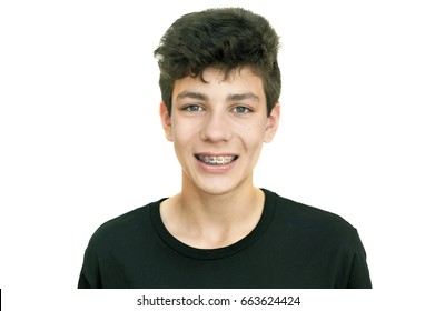 Beautiful teenager in a black shirt on a white background smiling. Clearly visible braces on teeth. Isolated