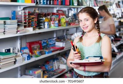 Beautiful teenager buying different products in stationery shop