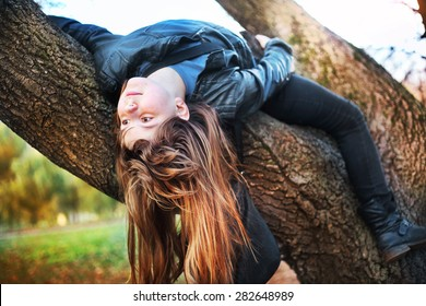 beautiful teenager girl with long blond hair climb tree