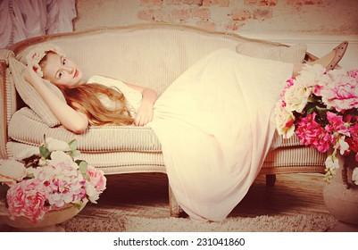 Beautiful teenager girl lying on sofa near flowers