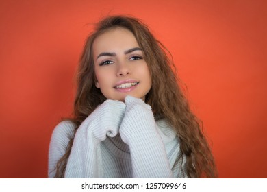 beautiful teenager girl portrait in white sweater on red backround
