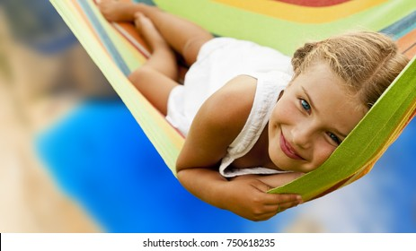 Beautiful teenager girl relaxing in the hammock on tropical beach with turquoise sea water, hot sunny day.
