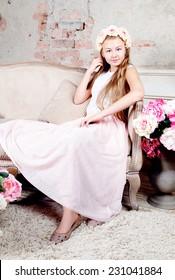 Beautiful teenager girl sitting on sofa and looking at camera