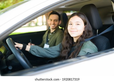 Beautiful teenager girl smiling and feeling happy sitting inside a car during her driving exam to get a driver's license