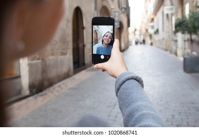 Beautiful teenager girl using smart phone camera taking selfies with hand holding device in city destination street, networking holiday outdoors. Photo on screen, smiling with technology lifestyle.