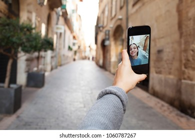 Beautiful teenager girl using smart phone camera taking selfies with hand holding device up in city street, networking on holiday, outdoors. Photo on device screen, smiling with technology lifestyle.