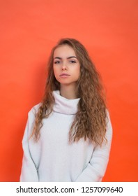 beautiful teenager girl in white sweater on red background