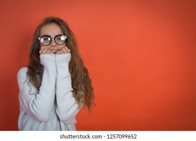 beautiful teenager girl in white sweater and glasses on red background