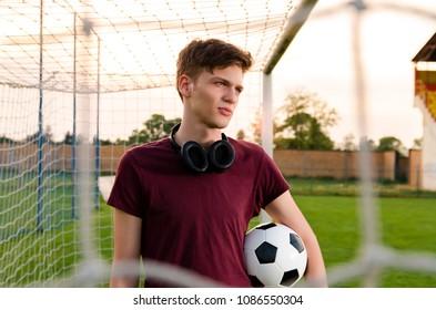 Beautiful teenager holding soccer ball , footballer , soccer player, standing in goal