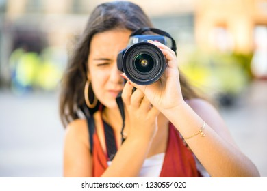 Beautiful teenager with long dark hair focused on taking photography in urban scenic