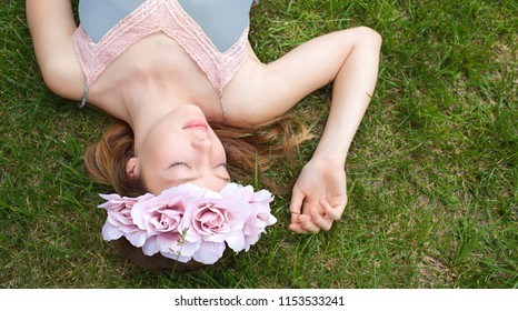 Beautiful teenager nordic girl laying on garden green grass wearing pink floral tiara, eyes closed, romantic dreamy femininity, outdoors. Portrait of young woman with flowers, beauty lifestyle.