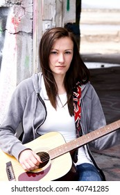 Beautiful Teenager Playing Guitar in an old abandoned Building
