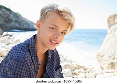 Beautiful teenager tourist male visiting rocky beach on a sunny day, smiling outdoors against blue sky. Young man leisure recreation lifestyle, travel nature space. Healthy wellness youth beauty.