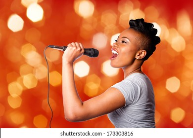 Beautiful teenager woman singing karaoke concert artist holding microphone, on red orange blurred lights background.