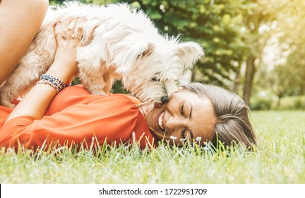 Beautiful teenager woman smiling and having fun with her white dog lying on the grass at the park. Dog licking and kissing owner