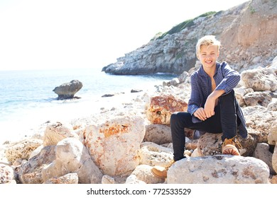 Beautiful teenager young man relaxing sitting on a rocky beach on a sunny holiday destination, looking at camera, smiling in nature, outdoors. Healthy living, travel well being recreational lifestyle.