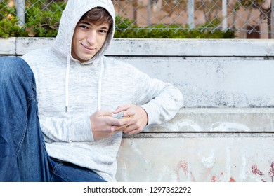 Beautiful teenager young man in urban grunge sport ground city outdoors, holding smartphone networking. Fashionable male using technology, looking smiling. Leisure recreation lifestyle.