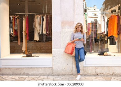 Beautiful teenager young woman in city shopping street by fashion store window, smiling using a smartphone to network online, outdoors. Adolescent consumer using technology, lifestyle exterior.