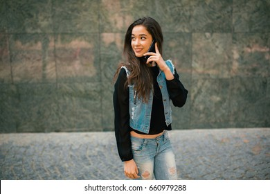Beautiful teens talk to smartphone dressed in jeans, and have fun in the city