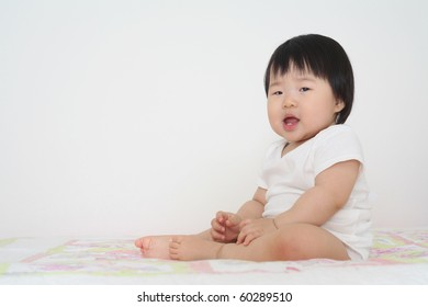 Beautiful ten month old asian baby infant girl in white body suit sitting up and babbling with mouth open