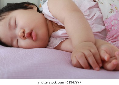 Beautiful ten month old asian baby infant girl in pink and white bodysuit fast asleep