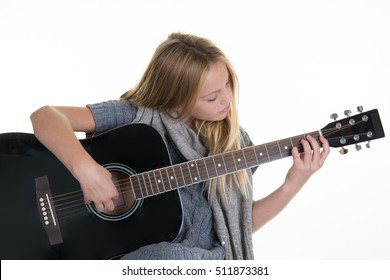 Beautiful ten year old with acoustic guitar over white