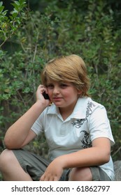 Beautiful ten years' boy with light golden hair talking on a mobile phone
