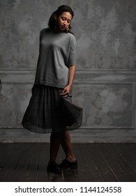Beautiful tender African-American young woman in grey shirt and black skirt standing with crossed legs on shabby wooden floor with closed eyes over background of old grey wall