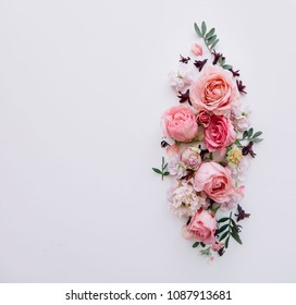 Beautiful tender blossoming floral frame of pink roses, eustoma, mattiola, tulips, eucalyptus on the white background, top view, flat lay