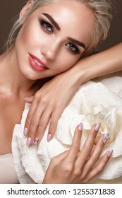 Beautiful tender girl with natural make-up and designer manicures with flowers. Beauty face. Photo taken in the studio