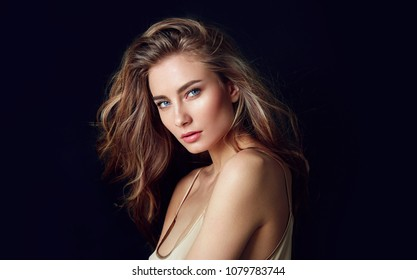 A beautiful tender girl in a silk top with beautiful long dark hair developing in the wind. Black background.fashion, beauty, makeup, cosmetics, beauty salon, style, personal care, posture, hair, hair